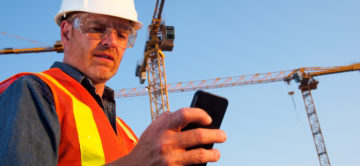 A royalty free image from the construction industry of an engineer or construction worker using a smart phone to text or make a call at a construction site.